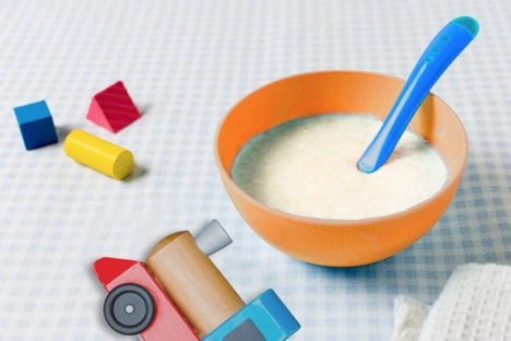 Baby weaning or spoon feeding - bowl of food for babies, in a table with toys